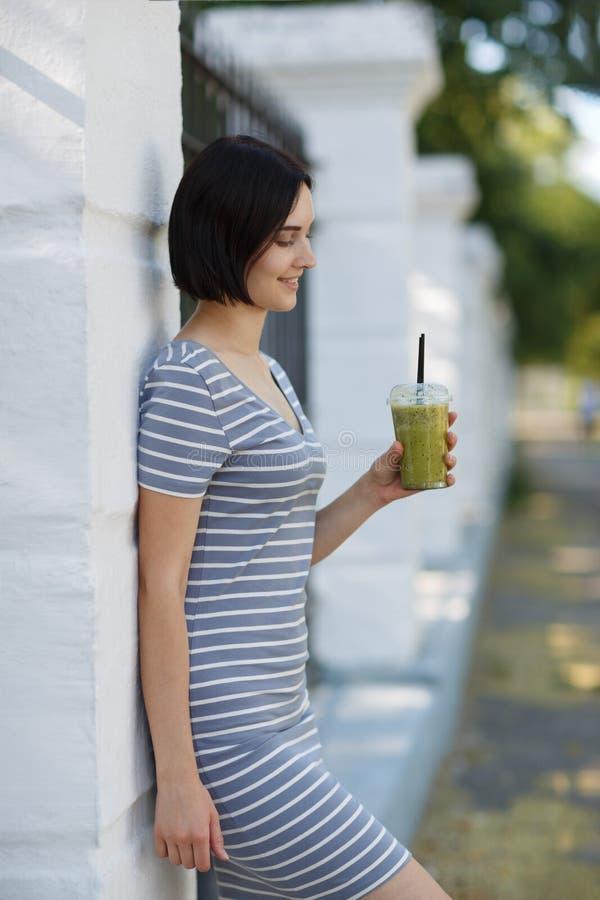 Mulher bonita com um cocktail verde Uma mulher bonita que inclina-se em uma parede em um fundo natural Conceito ocasional da form imagem de stock royalty free