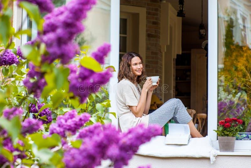 Mulher bonita com um copo da bebida quente fotos de stock royalty free