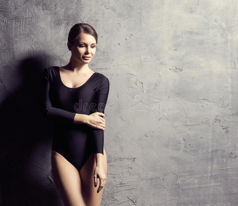 Mulher bonita com um corpo perfeito Menina que levanta e que dança no roupa de banho Foto do estúdio sobre o fundo concreto imagens de stock royalty free