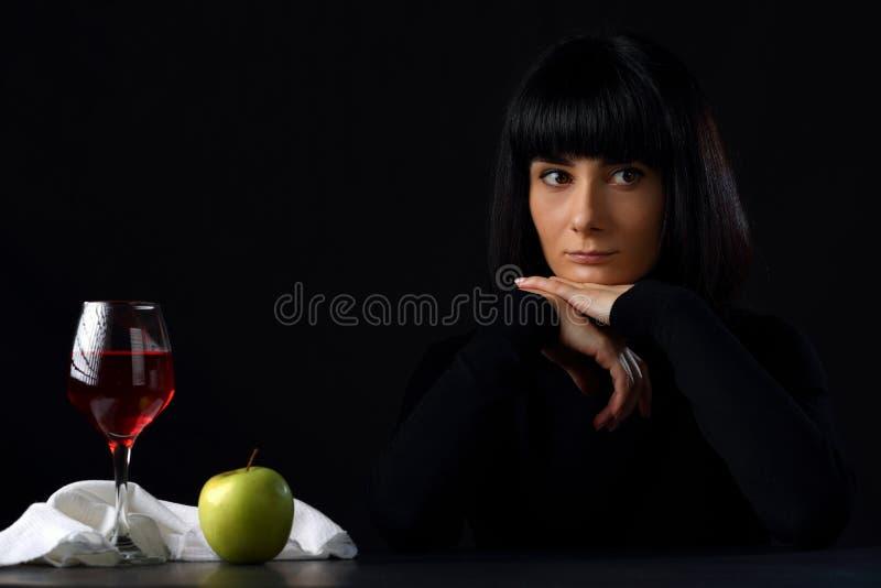 Mulher bonita com um vidro do vinho e de uma maçã imagens de stock royalty free