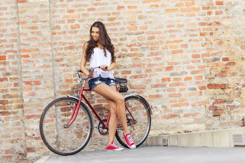 Mulher bonita com uma bicicleta vermelha velha na frente da parede de tijolo foto de stock royalty free