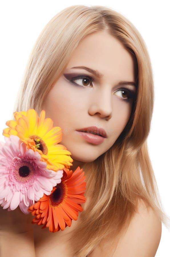 A mulher bonita com uma flor do Gerbera isolada no branco fotos de stock