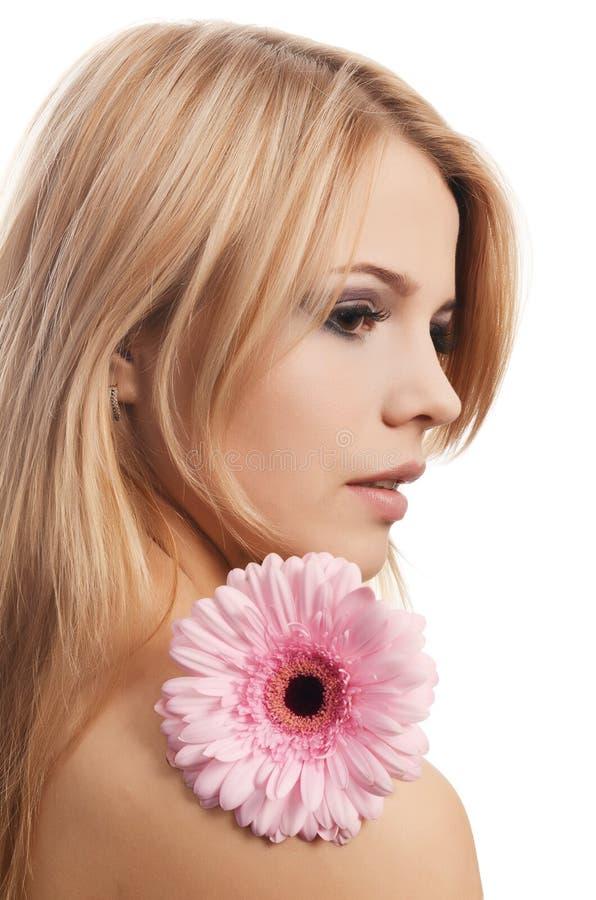 A mulher bonita com uma flor do Gerbera isolada no branco imagem de stock