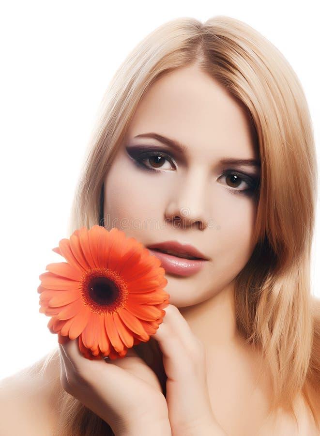 A mulher bonita com uma flor do Gerbera isolada no branco fotos de stock royalty free