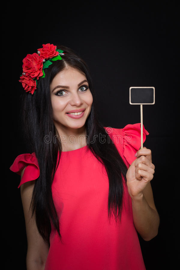 A mulher bonita com uma grinalda de flores vermelhas guarda uma chapa de madeira fotos de stock royalty free