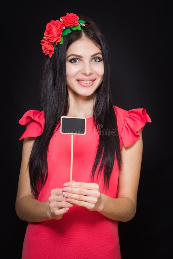 A mulher bonita com uma grinalda de flores vermelhas guarda uma chapa de madeira imagens de stock royalty free