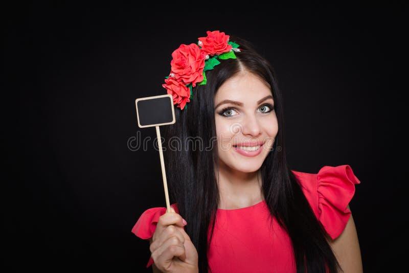 A mulher bonita com uma grinalda de flores vermelhas guarda uma chapa de madeira fotografia de stock royalty free