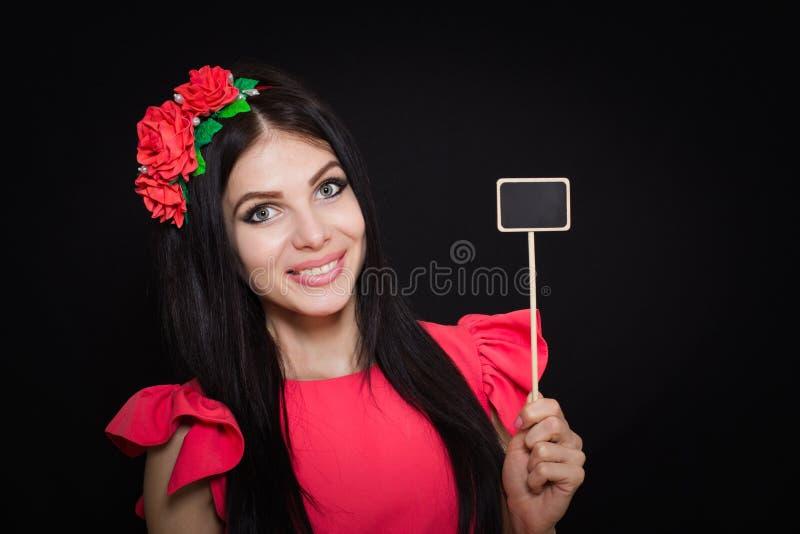 A mulher bonita com uma grinalda de flores vermelhas guarda uma chapa de madeira imagem de stock