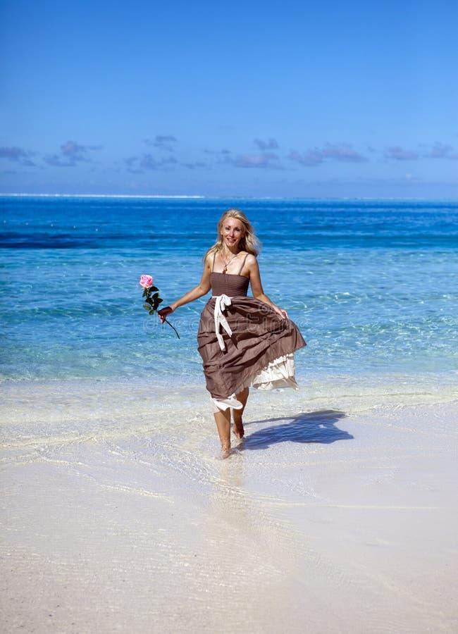 A mulher bonita com uma rosa corre na borda do mar em uma praia polynesia fotografia de stock