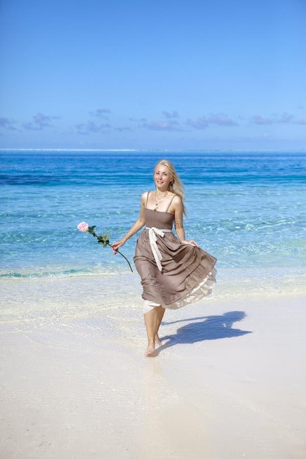 A mulher bonita com uma rosa corre na borda do mar em uma praia polynesia imagens de stock royalty free