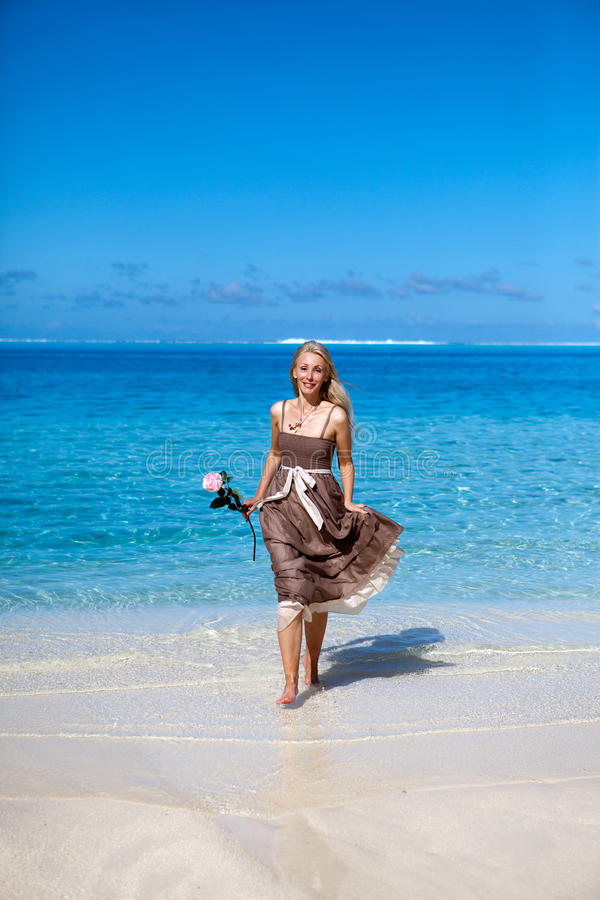 A mulher bonita com uma rosa corre na borda do mar em uma praia polynesia imagem de stock royalty free
