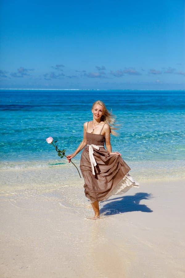 A mulher bonita com uma rosa corre na borda do mar em uma praia polynesia fotos de stock royalty free