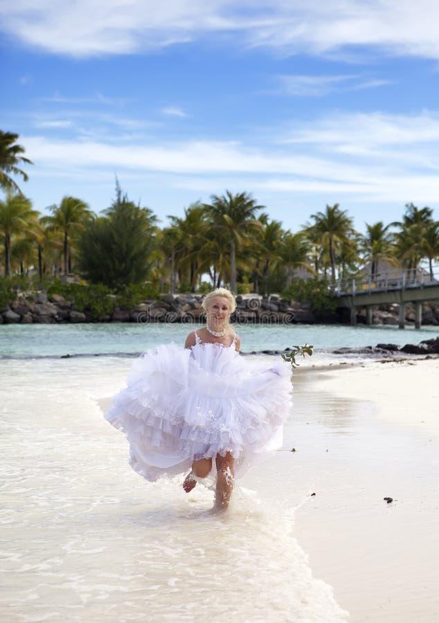 A mulher bonita com uma rosa corre na borda do mar em uma praia polynesia fotografia de stock royalty free