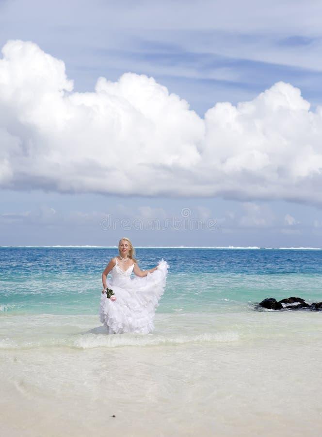 A mulher bonita com uma rosa corre na borda do mar em uma praia polynesia imagens de stock