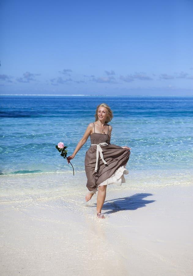 A mulher bonita com uma rosa corre na borda do mar em uma praia polynesia imagem de stock