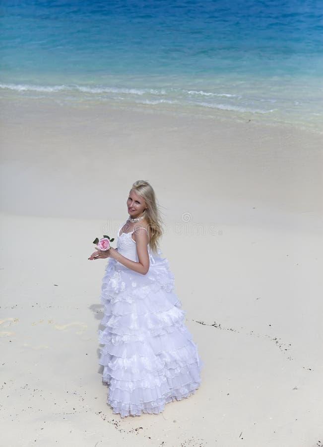 A mulher bonita com uma rosa na borda do mar em uma praia polynesia foto de stock