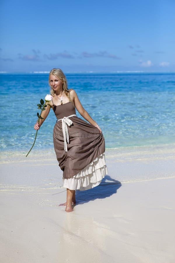 Mulher bonita com uma rosa na borda do mar em uma praia polynesia fotos de stock