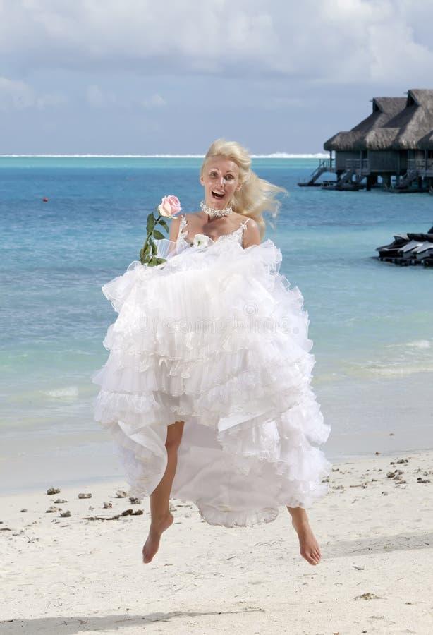 A mulher bonita com uma rosa que salta na borda do mar em uma praia polynesia imagens de stock