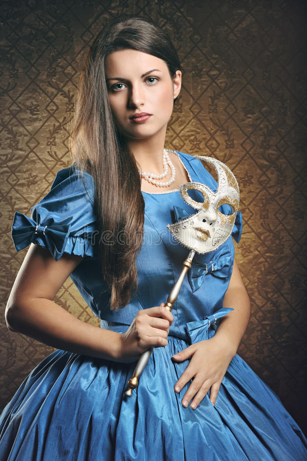 Mulher bonita com vestido azul e máscara venetian imagem de stock