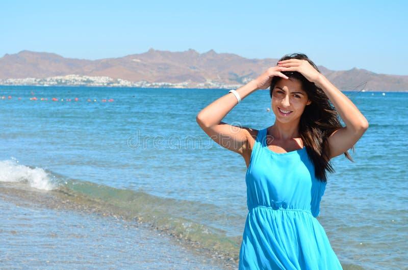 Mulher bonita com vestido azul em um fundo do mar imagens de stock