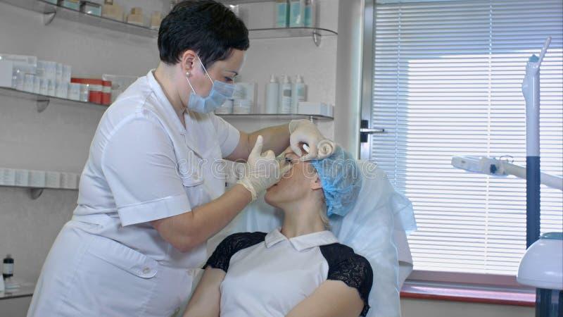 A mulher bonita começ uma injeção em sua face foto de stock royalty free