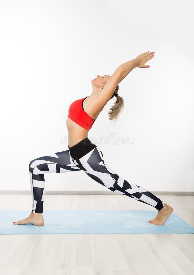A mulher bonita da aptidão que estica os pés que fazem o pé dos pilates estica exercícios no gym fotografia de stock