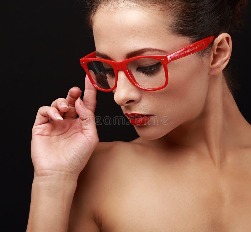 A mulher bonita da composição no vermelho eyes os vidros que olham para baixo closeup imagens de stock royalty free
