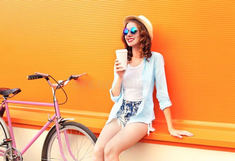 A mulher bonita da forma bebe o café do copo perto da bicicleta retro do rosa do vintage sobre a laranja colorida fotografia de stock