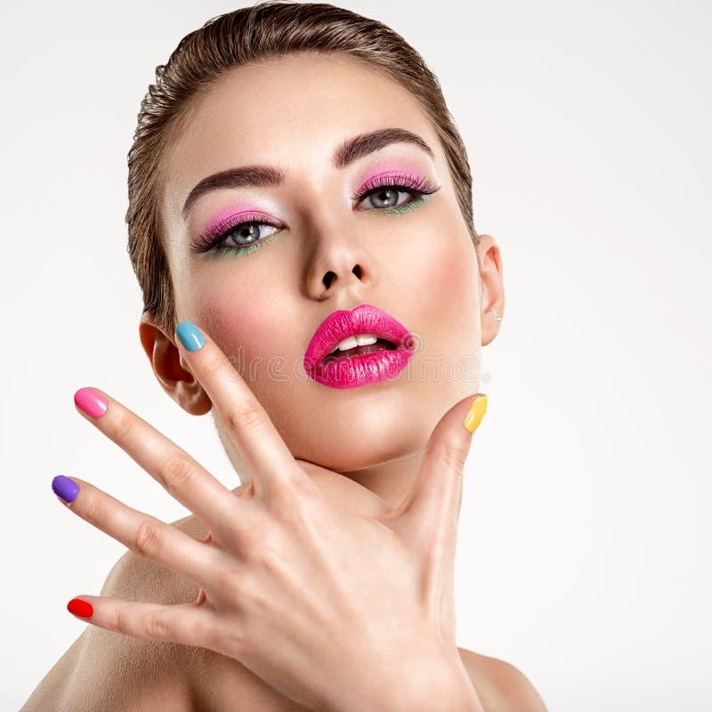 Mulher bonita da forma com pregos coloridos Menina branca atrativa com tratamento de mãos multicolorido imagem de stock royalty free