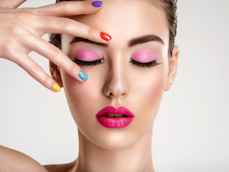 Mulher bonita da forma com pregos coloridos Menina branca atrativa com tratamento de mãos multicolorido fotos de stock