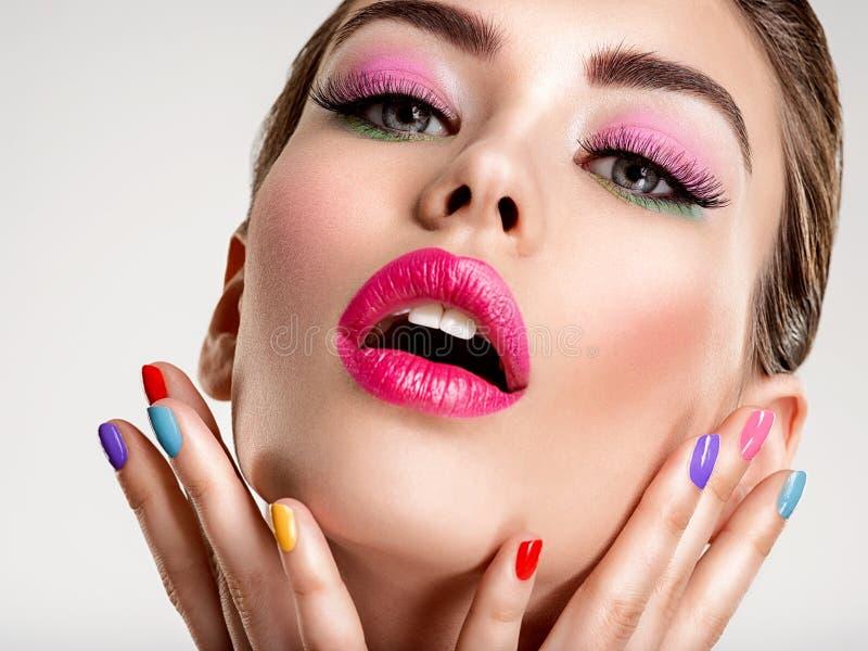 Mulher bonita da forma com pregos coloridos Menina branca atrativa com tratamento de mãos multicolorido fotografia de stock royalty free