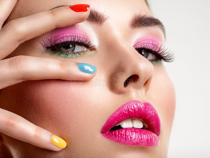Mulher bonita da forma com pregos coloridos Menina branca atrativa com tratamento de mãos multicolorido foto de stock royalty free