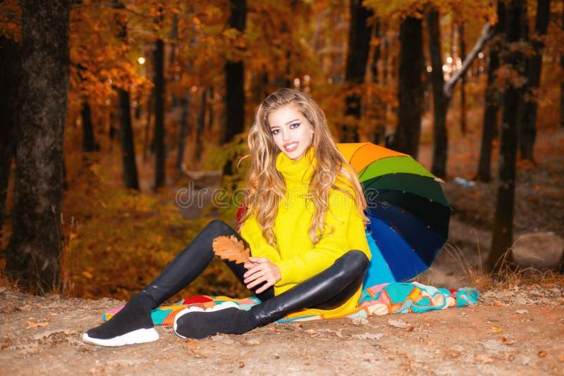 A mulher bonita da forma no vestido vermelho do outono com queda sae sobre o fundo da natureza Jovem mulher despreocupada em na m fotografia de stock