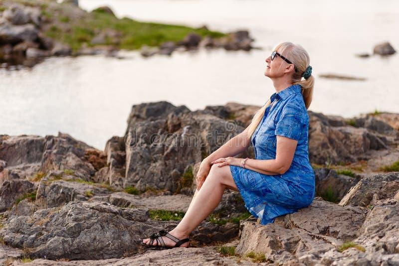 Mulher bonita da idade da reforma no perfil em um vestido azul que senta-se em uma pedra perto do rio no por do sol imagens de stock