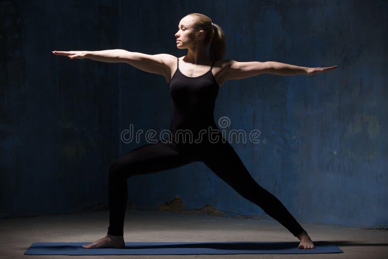 Mulher bonita da ioga que faz a pose do guerreiro II imagem de stock