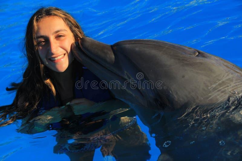 Mulher bonita da menina que beija golfinhos felizes de sorriso de um nariz da garrafa da nadada da criança da cara da aleta lindo fotografia de stock