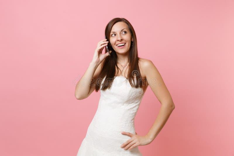 Mulher bonita da noiva no vestido de casamento branco que fala no telefone celular, conversação agradável de condução sobre imagens de stock