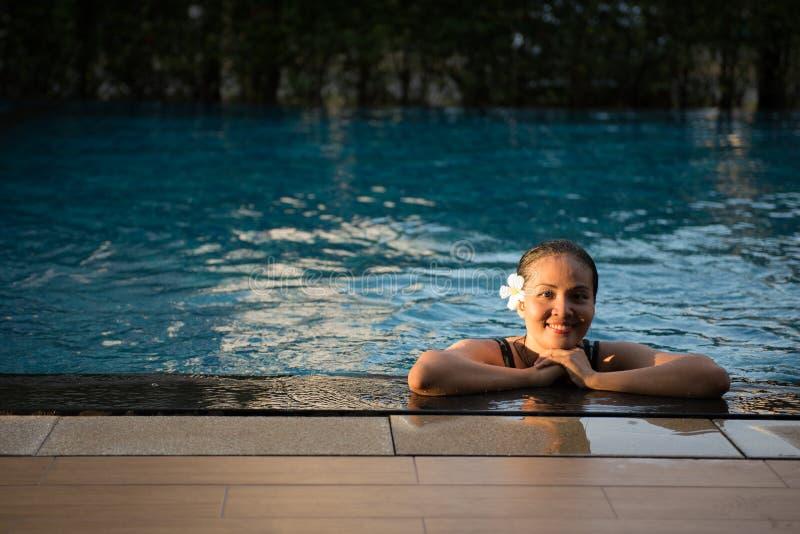 Mulher bonita de Ásia que relaxa na borda da piscina fotografia de stock royalty free