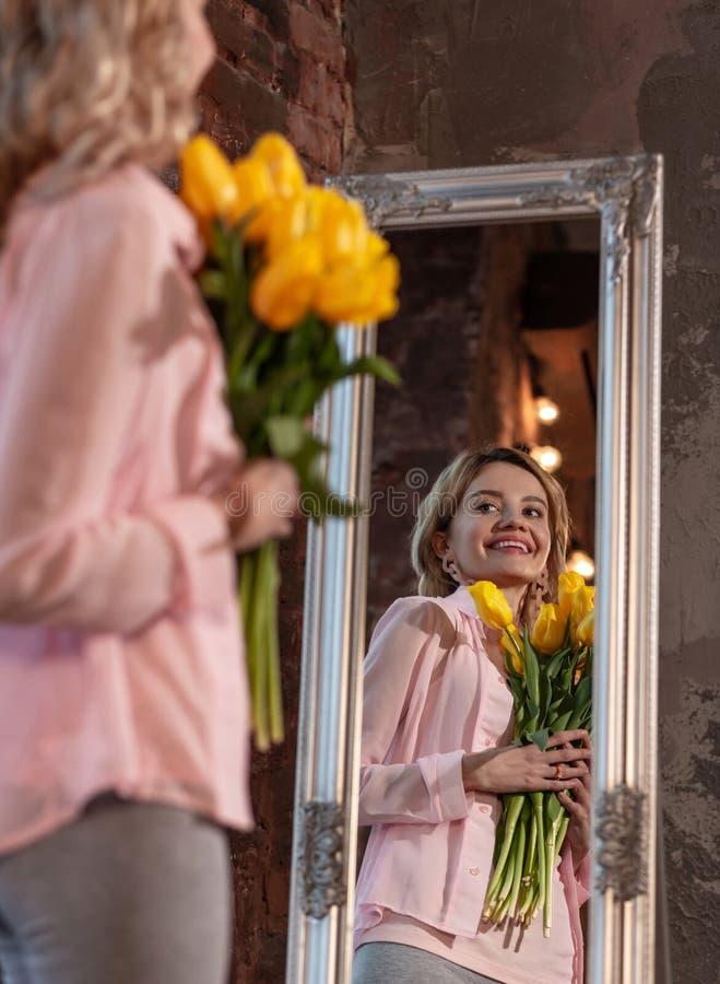 Mulher bonita de irradiação que guarda flores e que olha no espelho fotos de stock royalty free