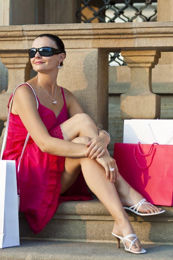 Mulher bonita de Latina que relaxa com sacos de compra imagens de stock royalty free
