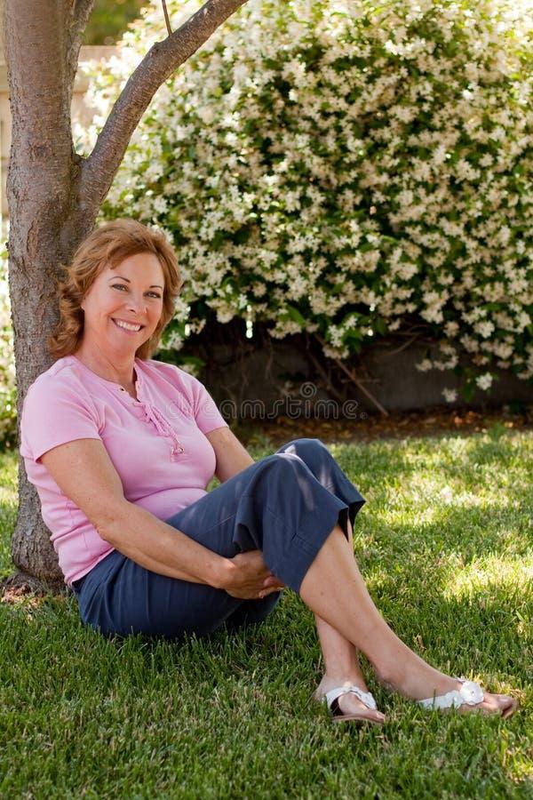 A mulher bonita, de meia idade senta-se sob a árvore imagens de stock royalty free