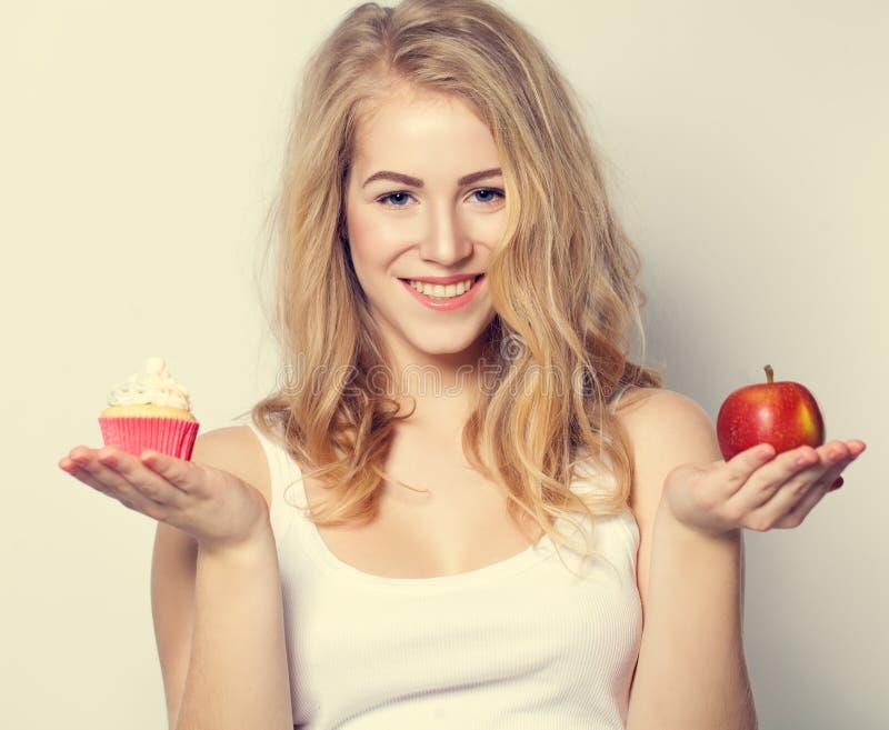 Mulher bonita de sorriso com alimento saudável e insalubre fotografia de stock royalty free