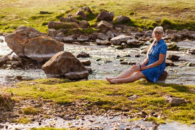 Mulher bonita de sorriso da idade da reforma em um vestido azul que senta-se em uma pedra perto do rio no por do sol imagem de stock royalty free