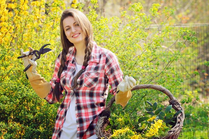 Mulher bonita de sorriso em um jardim completamente das flores imagens de stock royalty free