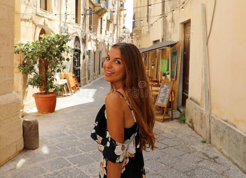 Mulher bonita de sorriso feliz no passeio florescido do vestido do verão alegre e alegre em Siracusa, Itália Forma bronzeada 'sex fotos de stock