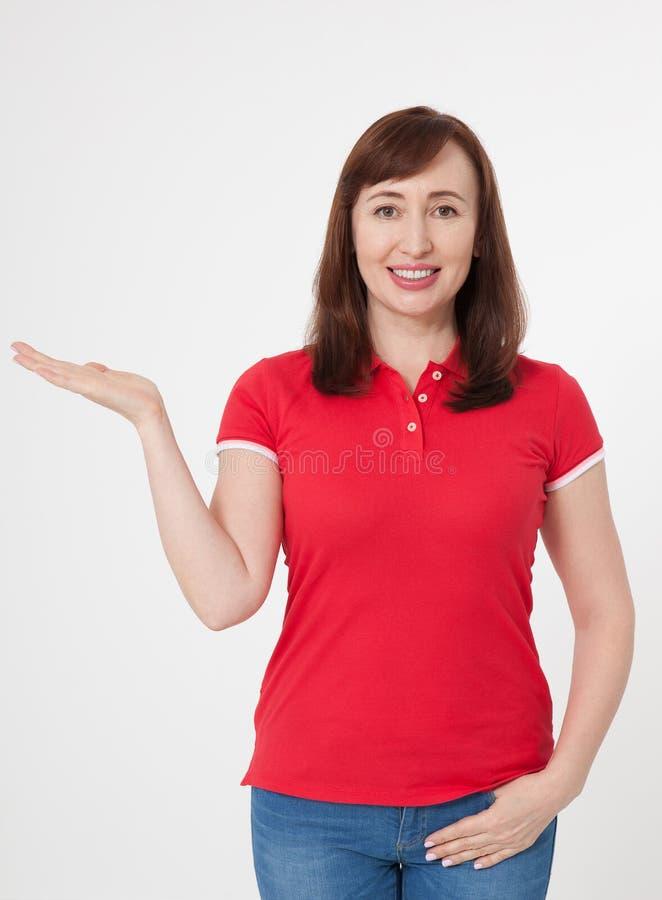 A mulher bonita de sorriso na camisa do vermelho t e na calças de ganga e em mostrar vazios algo por sua mão, zomba acima no fund fotografia de stock royalty free