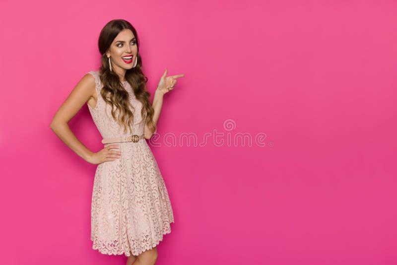Mulher bonita de sorriso no laço bege Mini Dress Is Looking Away, apontando e fala imagem de stock