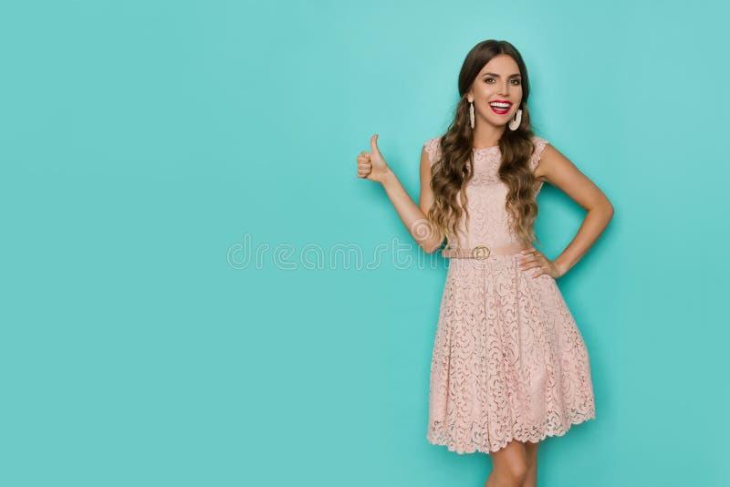 Mulher bonita de sorriso no laço bege Mini Dress Is Showing Thumb acima fotos de stock royalty free