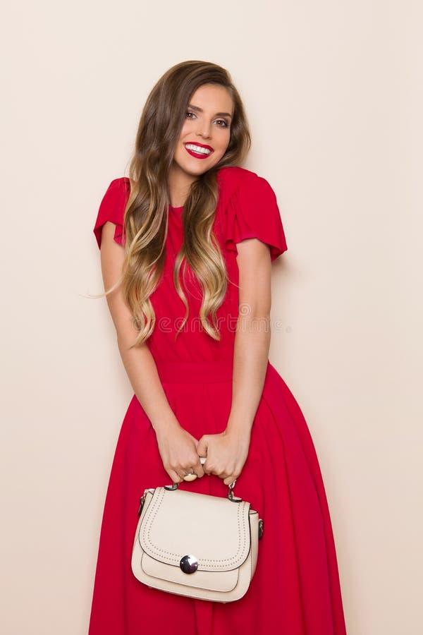 Mulher bonita de sorriso no vestido vermelho com bolsa bege imagens de stock royalty free