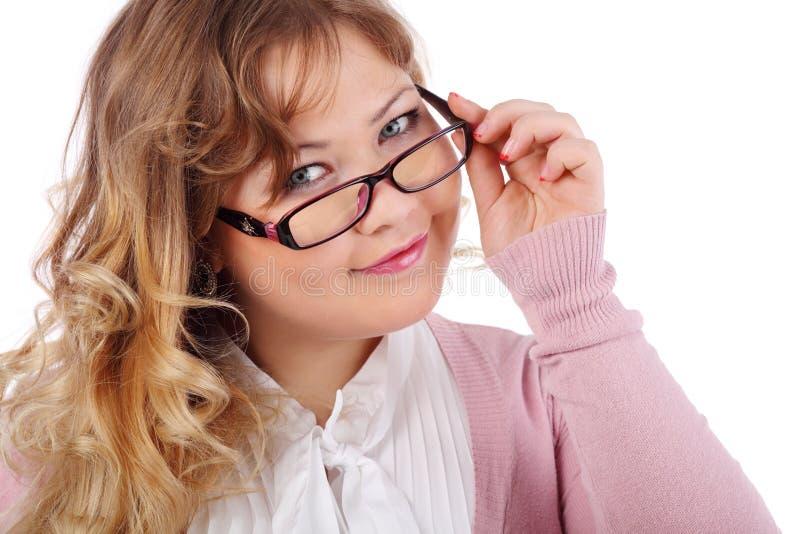 A mulher bonita de sorriso nos vidros olha a câmera foto de stock